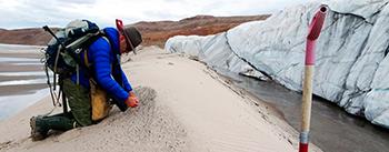 Geologen Kurt H. Kjær indsamler prøver af smeltevandssand foran Hiawatha gletsjeren. Sandet, som gletsjeren har ført med sig fra bunden af meteorkrateret, har givet en rigdom af oplysninger om meteornedslaget (tekst: GEUS. Foto: S. Funder).