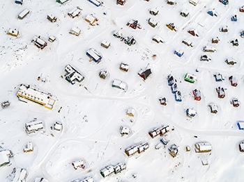 Luftfoto af Ittoqqortoormiit, Østgrønland. Klimaændringer er den største trussel for isbjørnene. Efterhånden som havisen omkring bygden bliver mindre og mindre, tilbringer isbjørnene længere tid på land og dukker op inde i bygden. I de senere år har der været en bekymrende stigning i møder mellem isbjørne og mennesker i hele Østgrønland (©James Morgan/WWF-UK).